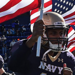 Navy football players with U.S. Flag